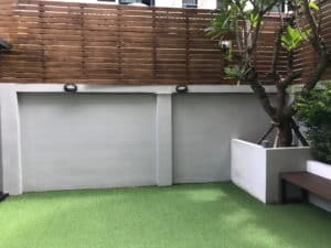 Gray concrete wall with attractive wood panels and green