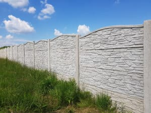Stone styled precast wall on grass with blue sky