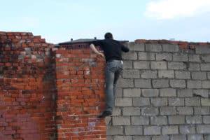 Man climbing over brick wall