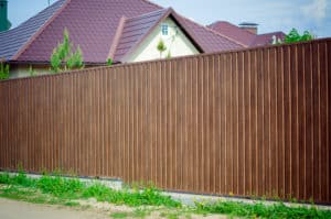 Dark brown trex styled fence in front of home