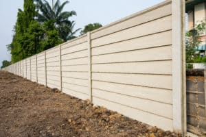 Precast wall with palm trees and dirt