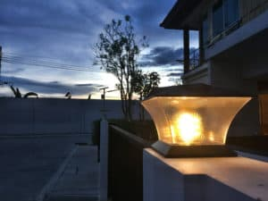 Contemporary solar powered lamp on top of concrete fence post surrounding a home