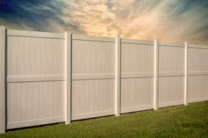 White vinyl fence on green grass and beautiful sky