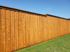 Solid wooden fence on green grass with blue sky above
