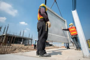 Workers installing precast wall at large construction site