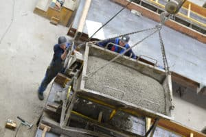 Workers filling a precast concrete mold
