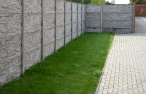 Durable gray concrete fence around grass and sidewalk