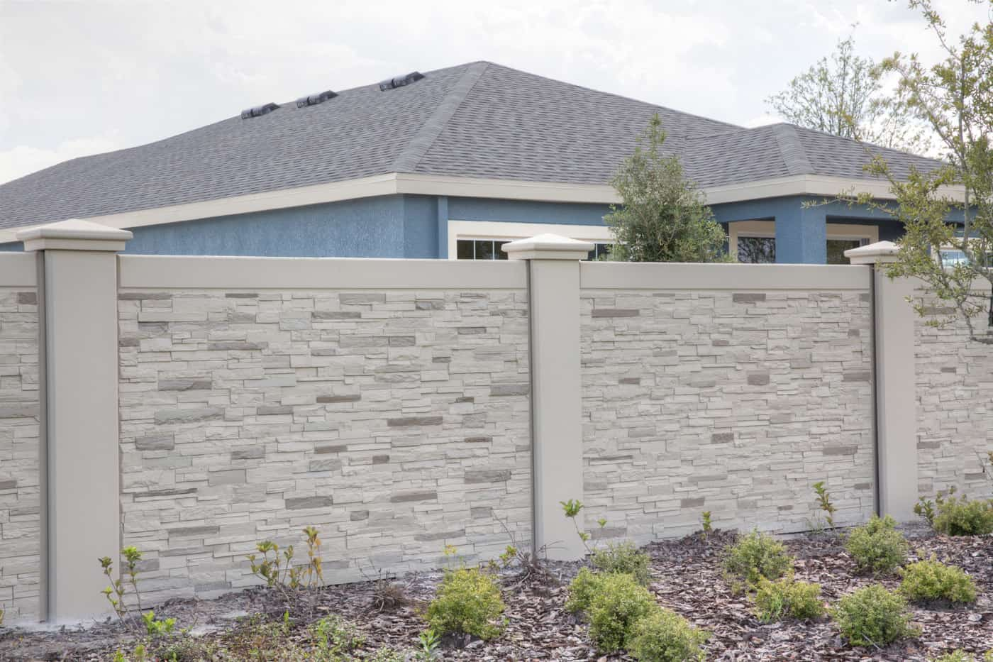precast stone fence in front of blue house