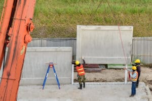 Construction workers installing a concrete wall