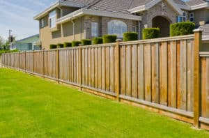 Nice wood fence on green lawn surrounding home